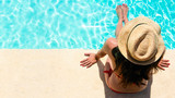 Fototapety Woman sitting in a swimming pool with a sunhat