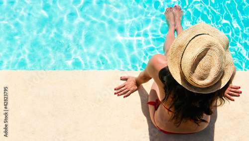 Woman sitting in a swimming pool with a sunhat
