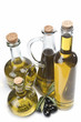 Botellas con aceite de oliva y aceitunas negras sobre blanco