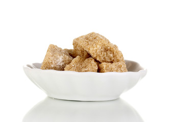 Lump brown cane sugar cubes on saucer isolated on white