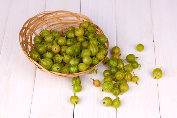 Green gooseberry in basket on wooden background