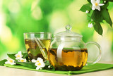 Fototapety green tea with jasmine in cup and teapot