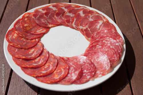 Salchichon, Chorizo and Cabecero sausage on white plate