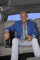 hombre de negocios sujetando un teléfono en un auto.