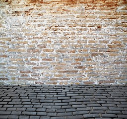 old brick wall with cobblestone street