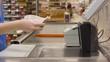 cashier counts money in supermarket