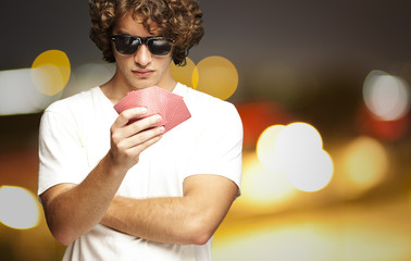 portrait of young man wearing sunglasses and playing poker at ci