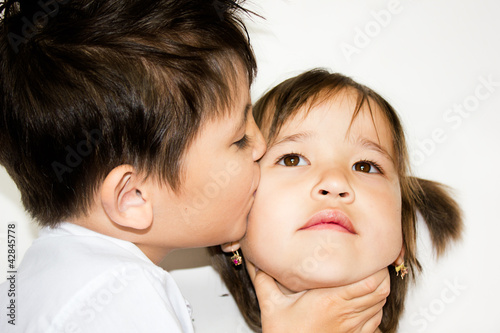 a boy kissing a girl on a white background