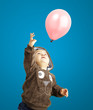 portrait of funny kid trying to hold a pink balloon over blue ba