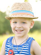 Portrait of young cute boy with blue eyes, wearing straw hat.