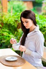 Junge Frau im Garten mischt Tee