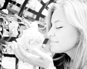 Pretty young woman smelling a rose