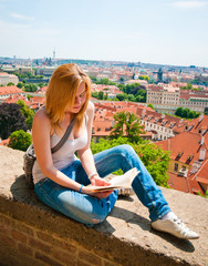 Woman sitting and reading in Prague