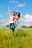 Two happy young women jumping