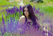Beautiful fashion woman among purple flowers