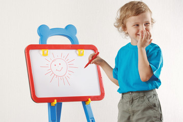 Little smiling cute boy drew a sun on the whiteboard