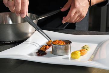 der Koch richtet das Essen an - in der Restaurantküche