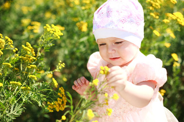Cute child girl in yelow flower field