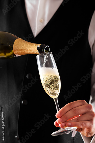 Waiter serving a glass of champagne