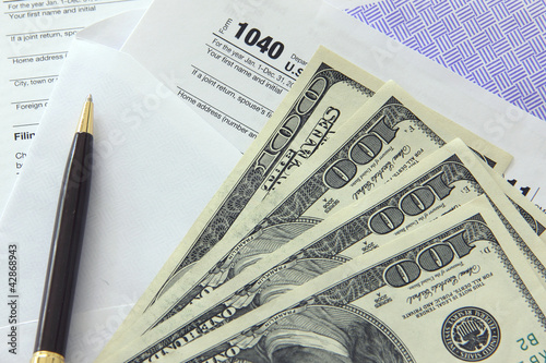 Tax papers with 100 dollar bills