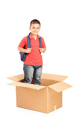 A child with backpack standing in a cardbox