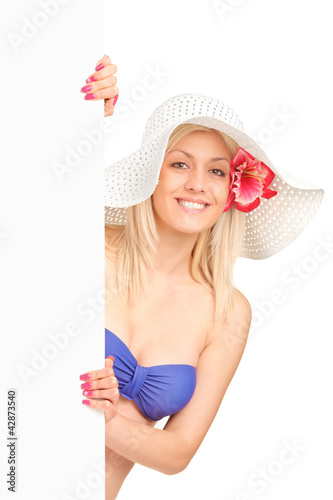 An attractive blond woman in swimsuit holding a white panel