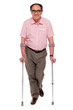 Smiling senior man walking with two crutches