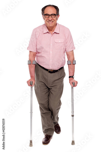 Smiling senior man walking with two crutches