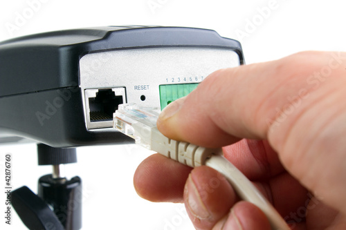 Hand inserting ethernet cable into network camera