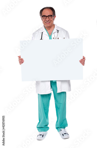 Confident doctor showing blank whiteboard