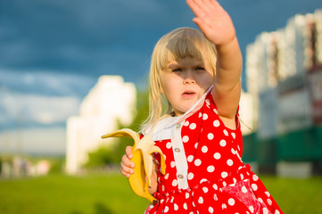 Adorable girl in beautiful dress eat banana with storm sky on ba