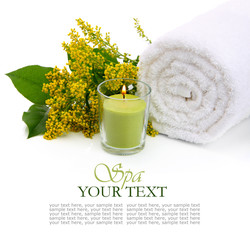 Spa setting with rolled towel, flowers and burning candle