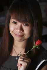 She holds a red rose.