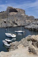 yacht and boat near rocky coast