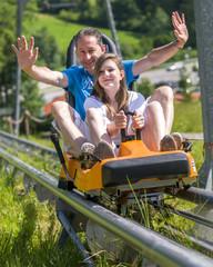 Papa mit Tochter beim Rodeln