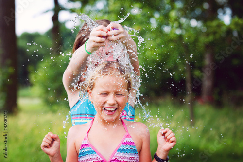 girls having fun outdoor with water balloons