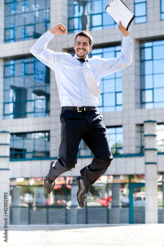 Happy businessman jumps in the air
