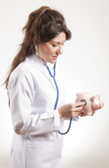 Female Doctor Holding Stethoscope to Pink Piggy Bank
