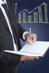 Businessman write on notebook with graph.