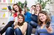 Teenagers showing mobile phones' screen