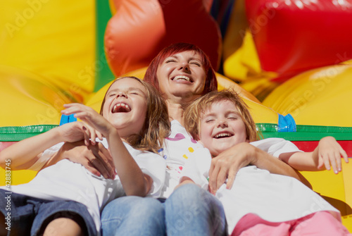 Mother and her daughters having fun on jumping castle