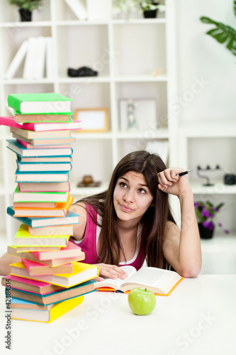 Unhappy student with big stack of books