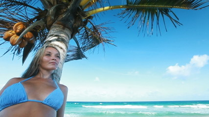 Young woman posing on the beach under the palm tree