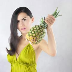 Zdenerwowana piękna kobieta z dojrzałym ananasem
