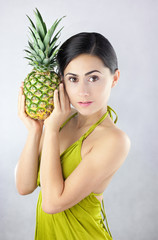 Kobieta w zielonej sukience trzymająca w dłoniach ananasa