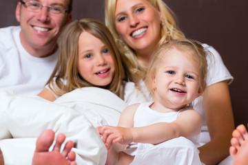 Familie mit Kindern im Schlafzimmer