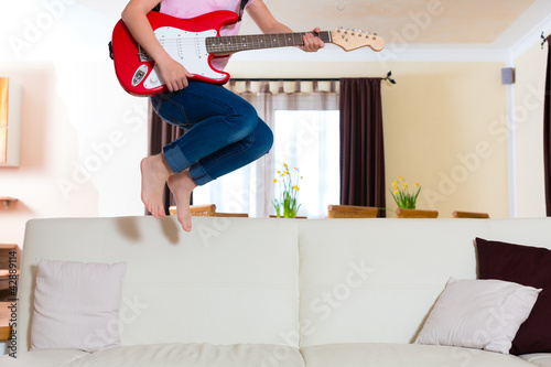 Child jumping with guitar on the couch