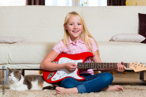 Child with guitar making music