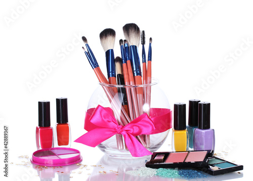 make-up brushes in glass vase and cosmetics isolated on white