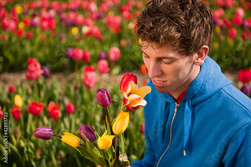 Young man is picking flowers